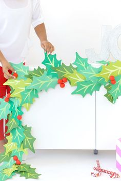 Decorate your mantle with a gorgeous DIY paper garland that shows off your holiday spirit! This tutorial for how to make a paper garland uses die cutting to create its holly leaves and is accented with red holly berries made from Styrofoam. Kfc Christmas, Christmas Stage, Diy Christmas Garland, Christmas Craft Projects, Christmas Program, Christmas Paper Crafts, Diy Garland, Holiday Crafts, Christmas Holidays