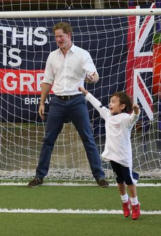 A young boy celebrates after scoring a goal against Prince Harry during a visit to Minas Tenis Clube on the second day of his tour of Brazil on June 24, 2014