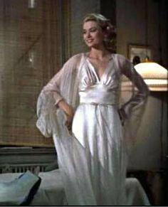 """Grace Kelly wears a silky negligee in a movie still from the 1954 murder-mystery, """"Rear Window."""" Costume designer Edith Head recalled Kelly giggling upon spotting her reflection in the mirror. """"Why, I look like a peach parfait!"""" she said."""