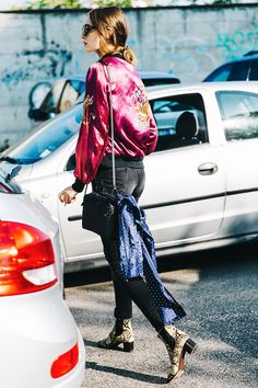 An embroidered silk bomber jacket is paired with jeans, a shoulder bag, silk scarf, and snake-print boots