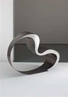 this chair by Ron Arad is simple and has a huge gaping whole through it. It is silver and has smooth curves