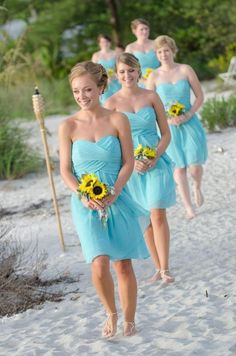 bridesmaids in teal dresses with sunflower bouquets and foot jewelry for a beach wedding