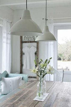 farmhouse dining room with wood plank table, simple centerpiece and ladder against the wall