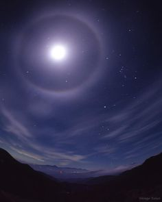 Photo of a lunar halo. The stars of Orion are in the top right, along with the constellations Taurus (the bull) above it and Canis Major (the big dog) below it. The three constellations surround the glowing lunar halo. Lunar and solar halos are caused when light passes through ice crystals formed in clouds in Earth's atmosphere. Ice crystals in a high, thin layer of cirrus clouds bend the light at a specific angle like a lens. Photo by astrophotographer Shingo Takei.