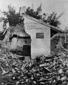 """WWI Italian front - Veneto - Foto scattata nel 1915: desolazione e macerie al fronte del Piave. Una scritta """"tiranneggia"""" sui muri della casa distrutta: """"tutti eroi! o il Piave o tutti accoppati!"""""""