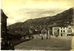 """Nedre Torvet, med Kjøttbazaren i sentrum der i bakgrunnen..  Vi er i Bergen ca.1880, og ser nedover mot Nedre Torvet, og dens bygninger; boliger og butikker til høyre,og en del av Zachariasbryggens sjøhus til venstre. Og – så var det """"Kjødbazaren"""" helt der bak i midten av bildet: Denne ble godkjent for bygging i 1874, ferdigstilt i 1876, og tatt i bruk den 1. juli 1877.  Engelsktalende fotograf, – Ukjent."""