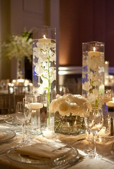 Centerpiece ideas. Tall class votives with white orchids and a low vase with white roses