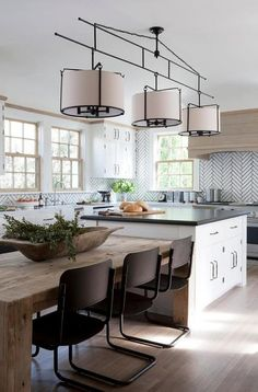 A three light drum pendant hangs over a white kitchen island topped with black quartz and a reclaimed wood dining table lined with vintage black dining chairs.