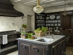 The kitchen island is made from a 19th-century cast-iron stove and topped with Carrara marble; the pendant light is early-20th-century French, and the walls are lined with 19th- century Portuguese tiles.   - ELLEDecor.com