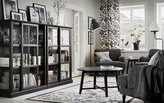 Nappali, sötétszürke fotelek, fekete dohányzóasztal, és két fekete üvegajtós szekrény, tolóajtókkal.