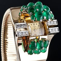 A glamorous bracelet watch by the renowned Parisian Joaillier - Mauboussin in collaboration with the renowned American jeweler - Trabert & Hoeffer of Chicago featuring shimmering clusters of bright green cabochon emeralds dotted with tiny diamond sparklers in between.