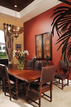 Beautiful wood, rich oranges and browns and a red accent wall combine to give this dining room a regal feel.