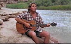 John Denver playing guitar by the water.