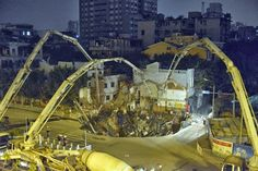 Workers use machinery to fill in a sinkhole that buildings collapsed into near a subway construction site in Guangzhou, south China's Guangdong province on January 28, 2013. The hole measured about 1,000 square feet across and was around 30 feet deep.