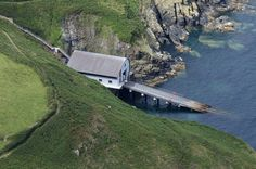 The RNLI Lizard Lifeboat Station in Kilcobben Cove, home to the 53ft Tamar class lifeboat Rose (16-20) official number 1300. There are 200 steps from the car park down to the building. Cornwall UK aerial image by John Fielding #rnli #lifeboat #station #cornwall #coast #aerial #kilcobben