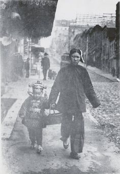 San Francisco Chinatown circa 1900    A family servant walks an elaborately dressed young boy along a street in San Francisco's Chinatown -- possibly a holiday trip to visit relatives. Photograph by Arnold Genthe.