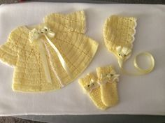 Infant baby sweater set, hat, and slip on booties. Crocheted from a 1940's pattern with delicate satin roses added to each ribbon.  White yarn accents each piece. Thank you for viewing, Bonnie.