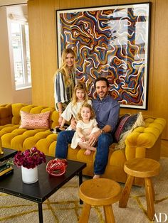 The Johnsons curl up on a vintage Edward Wormley sofa in the living room. Sol Lewitt painting; Jacques Quinet cocktail tables; Charlotte Perriand stools; on Chandra, top by Peter Pilotto.