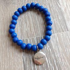 """Armband van 8mm clematis blauw hout met metalen """"Happiness"""". Van JuudsBoetiek, te bestellen op www.juudsboetiek.nl."""