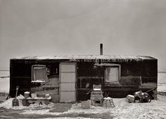 November 1936 near Dickens, Iowa. Three-room shack, the residence of L.H. Nissen, hired man for a tenant farmer. Farm is owned by a loan company. Ten people live in the shack: mother, father, seven children, one grandchild. Medium format negative by Russell Lee, Resettlement Administration.