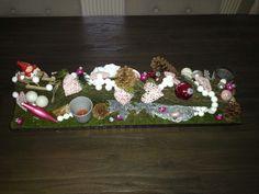 Groot kerststuk op oude plank, bekleed met nep-gras, met stuk afgezaagde boomtak en versiert met kerstspulletjes, kaarsjes ( appel-kaneel ) en lampjes (+/- 60×20cm groot)