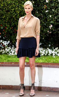 Charlize Theron in a nude top, black mini skirt and strappy heels