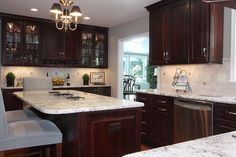Cabinets-cherry with chestnut stain, crestwood series hampton classic door, backsplash 4x4 tumbled Traventine, counter white spring granite Gorgeous Kitchen Remodel contemporary kitchen