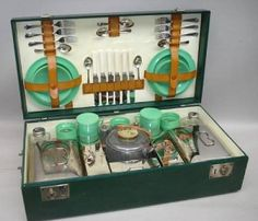 A Coracle six person picnic set, c1925,dark green Rexine cover, nickel plated handles and locks with key, opening to reveal cream interior fitted with Coracle ceramic based food boxes, wicker handled kettle with burner and stand, Coracle glass bottles, spirit flasks and other accessories, Bandalasta and other composite saucers, cups and plates some items replaced, cutlery housed in lid behind leather straps, two small spoons missing, case 65cm wide.
