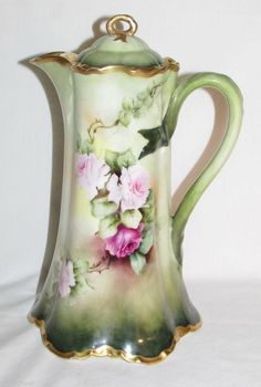 You are bidding on a Vintage HAVILAND Limoges Chocolate Floral Pitcher. This gorgeous pitched has an attractive unusual handle. This is Hand Painted with Gold Trim (slight wear to gold). It is in beau