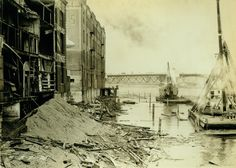 Demolition of old wharves and buildings along Portland's west side waterfront begins in this 1928 photo. The first pilings that will anchor the seawall cribbing outline the future wall's site. The Burnside Bridge is in the background; this was probably taken from somewhere near the foot of Oak Street.