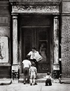 Shorpy Historical Photo Archive :: The Accordion Player: 1959 Taken in the Brownsville section of Brooklyn in 1959, on New Lots Avenue. This young man would come down to the street with his accordion and start to play. Invariably he would draw a number of children to his street concert. Notice his mother looking on approvingly from behind the door.
