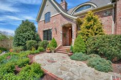 This attractive Tudor-style brick home features attractive landscaping along with a mostly traditional interior that includes a living room with stone fireplace, large kitchen, a variety of bedroom styles. Country Landscaping, Front Yard Landscaping, Landscaping Ideas, Red Brick Exteriors, Brick Facade, House Exteriors, Entrance Gates, Entrance Ideas, Walkway Ideas