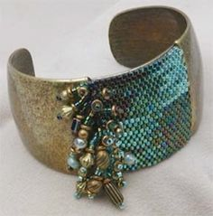 Cuff | Diane Hyde. Antique brass with flat Peyote stitched Delica beads and side fringes of assorted beads.