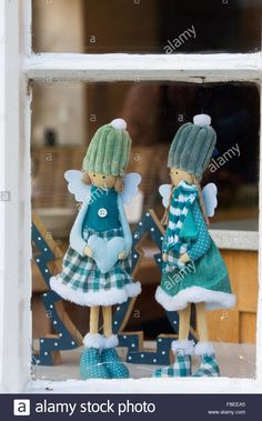 Two christmas angel dolls in a shop window. Cotswolds, England Stock Photo
