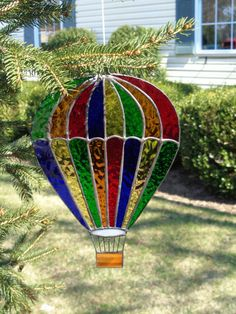 Here is a beautiful hot air balloon made in vibrant clear textured glass colored in deep blue, yellow, red, orange and green. It is accented by a brown streaked basket which is held by black strings which have been painted on a clear glass background which has very simple soft lines on it. The balloon is finished in black patina which make the bright colors pop. A piece of wire has been shaped and soldered to the top of the balloon for hanging. Dimensions: 8 1/2 X 6 1/2 Handmade it...
