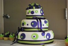 Modern three tier wedding cake with purple and green decorative circles.