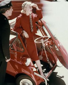 August 1957 Model emerging from a red BMW Isetta 300, is wearing a red wool dress and a cheetah lined jacket by Junior Sophisticates. ...