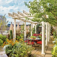 This rooftop dining area is situated right in the middle of fresh seasonal flowers, permanent trees and shrubs, and of course, edibles—which thrive on rooftops. | SouthernLiving.com