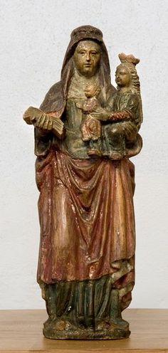 Sint Anna-te-Drieën  Eikenhout: hoogte 32 cm  Zuidelijke Nederlanden; 16e eeuw    Bij deze beeldgroep van Sint Anna-te-Drieën wordt Anna staande afgebeeld, met Maria op haar arm. Deze laatste draagt op haar beurt weer het kind Jezus.     Locatie: Petrus Banden kerk te Venray