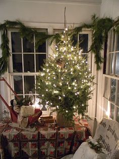 Prim Christmas Porch...lighted tree on an old quilt, toy sleigh, simple evergreen swag