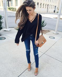 black lace-up top and ripped jeans