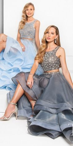 Stun the crowd at your next extravaganza in this Two Piece Rhinestone Cluster Embellished Tiered Prom Dress by Terani Couture. This chic style includes a cropped bodice that is fully embellished with clusters of rhinestones and has a matching waistband. The flared skirt includes multiple layers of iridescent fabric and a horse hair hem for a more dramatic appearance. The back of this style includes double straps for a unique look. #edressme