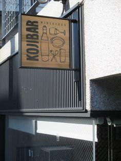 大阪府豊中市 KOJIBARコジバル様 ワインに合う日替わりのアラカルトを楽しめるバル。 木製看板にアイアンのブラケットで四方を囲んでステキな吊り下げ看板製作させていただきました。 Coffee Shop Signage, Signage Design, Logo Design, Small Restaurant Design, Blade Sign, Container Buildings, Store Image, Cafe Shop, New Dolls