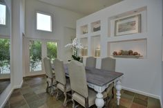 Light and bright dining room with windows and display shelves