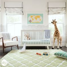 The bright rug and adorable design in this nursery are perfect for a newborn.