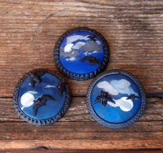Polymer clay Halloween jewelry - A round dark blue polymer clay frame with bats, clouds and moon, which glows in the dark