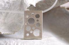 Zilveren ketting met drie verwisselbare kleuren acryl / plexiglas, geometrische hanger, modern abstract sieraad.  De halsketting bestaat uit een rechthoekig doosje van zilver waarin een uitneembare rechthoek van plexiglas is opgenomen. De hanger wordt geleverd met 3 verschillende kleuren acrylglas (paars, turquoise, violet), die gemakkelijk aan te brengen zijn in de hanger door het rubberen koord te verwijderen. Ook zonder plexiglas kan de ketting gedragen worden. Een andere mogelijkheid is…
