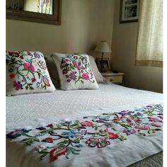 Pie de cama y almohadones bordados.