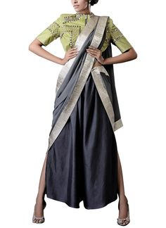This Kanelle outfit takes fusion wear to another level by combining a traditional blouse with palazzo pants and a stole that serves as a pallu. The grey palazzo pants are strategically cut to give them a wide-legged appearance with slits. The pants are paired with a lime green metallic hand studded blouse with a zipper at the front. Completing the saree look is a grey stole with a metallic border. Together, the three elements help you create a look that is eclectic, yet chic.