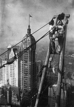 Constructions workers sit on a hoisting ball above the New York city skyline circa 1925♥נк∂